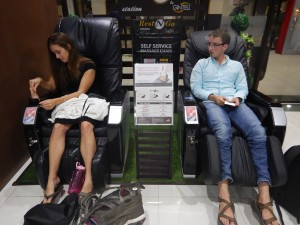 Ashley and Eli enjoying the massage chairs at the airport