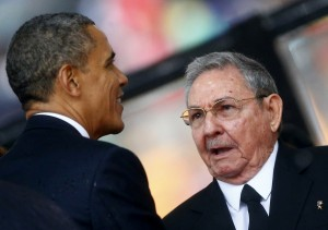 U.S. President Barack Obama (L) greets Cuban President Raul Castro before giving his speech at the memorial service for late South African President Nelson Mandela at the First National Bank soccer stadium, also known as Soccer City, in Johannesburg December 10, 2013. Obama shook the hand of Castro at a memorial for Nelson Mandela on Tuesday, a rare gesture between the leaders of two nations which have been at loggerheads for more than half a century. REUTERS/Kai Pfaffenbach (SOUTH AFRICA - Tags: POLITICS OBITUARY) - RTX16C61
