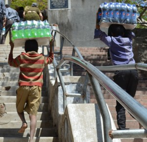 Young boys carrying sodas up almost 500 steps up a temple visited by tourists in Mount Abu, Rajasthan. It is the middle of the day.